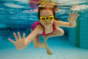 little girl underwater in pool